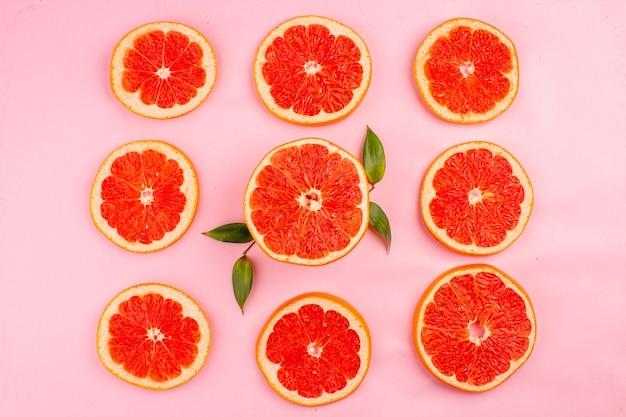 Vista dall'alto di gustosi pompelmi a fette di frutti succosi rivestiti sulla superficie rosa
