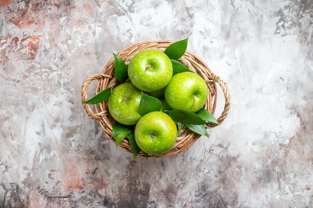 Top view tasty green apples inside basket on a light background
