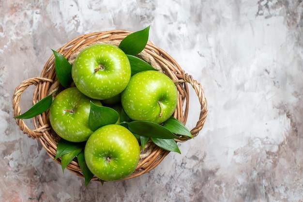 Vista dall'alto gustose mele verdi all'interno del cestello su sfondo chiaro