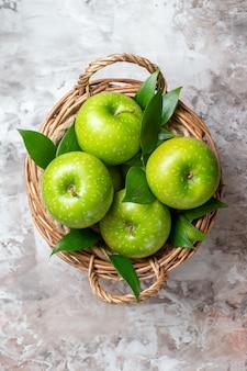Вид сверху вкусные зеленые яблоки внутри корзины на светлом фоне