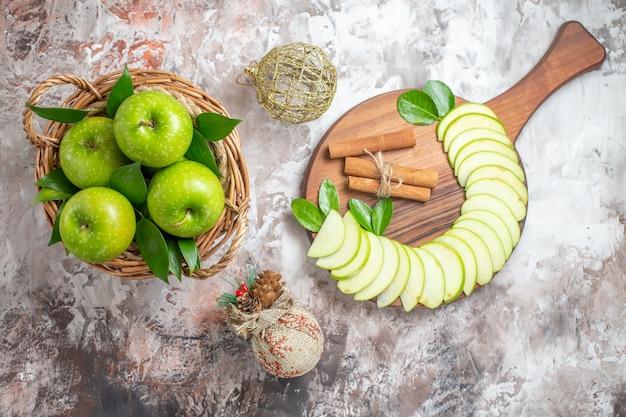 Vista dall'alto gustose mele verdi con frutta a fette sul pavimento chiaro