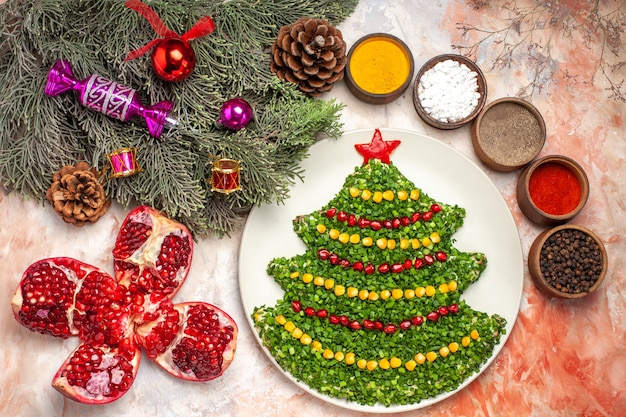 Top view tasty green salad in christmas tree shape with seasonings on light background
