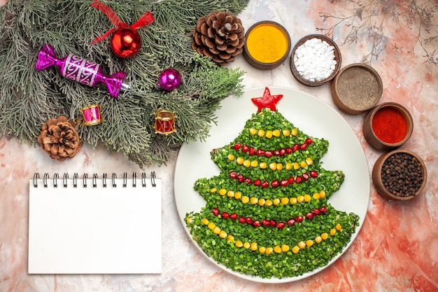 Top view tasty green salad in christmas tree shape with seasonings on light floor holiday color photo meal health xmas