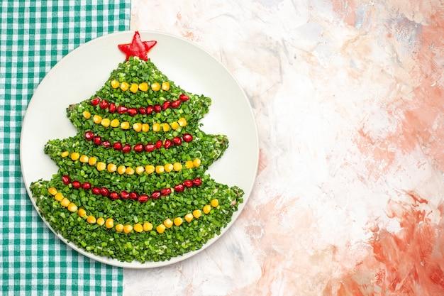 明るい背景の上のクリスマスツリーの形でおいしいグリーンサラダの上面図