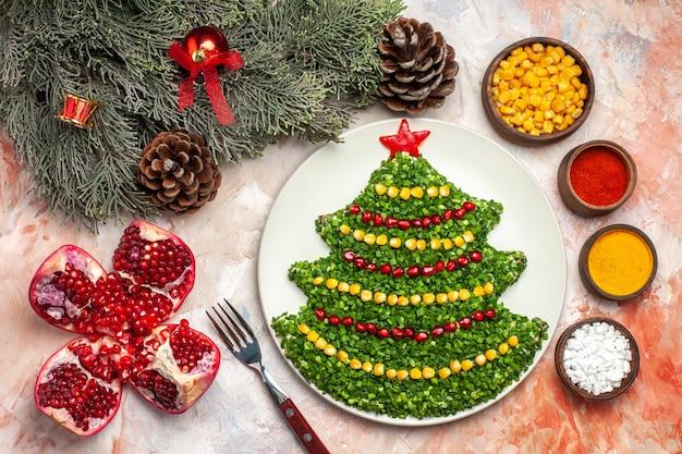 밝은 배경에 조미료와 크리스마스 트리 모양의 상위 뷰 맛있는 그린 샐러드