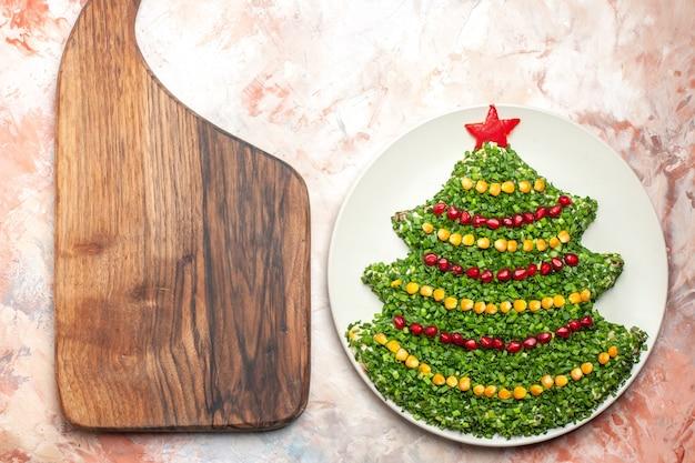 밝은 배경에 접시 안에 새 해 나무 모양의 상위 뷰 맛있는 그린 샐러드