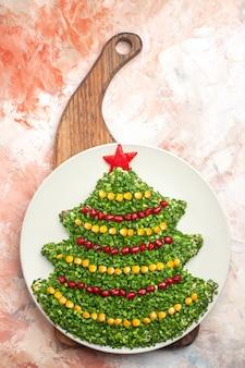 Вид сверху вкусный зеленый салат в форме новогодней елки внутри тарелки на светлом фоне