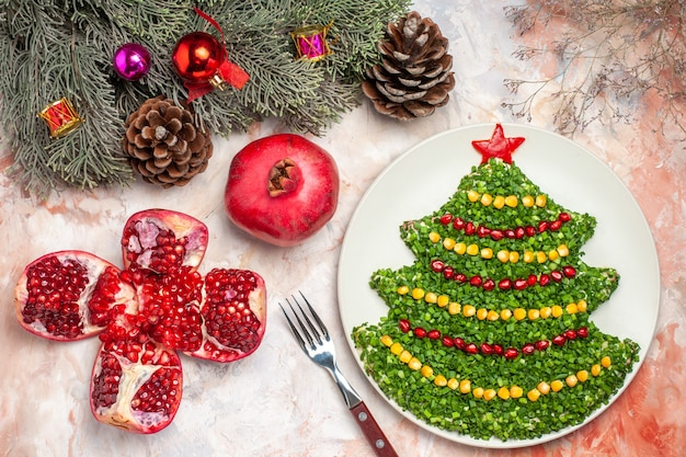 明るい背景の上の新年の木の形でおいしいグリーンサラダの上面図