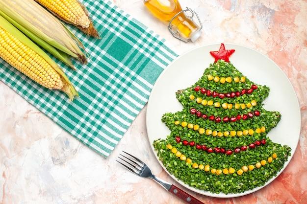 Вид сверху вкусный зеленый салат в форме новогодней елки на светлом фоне