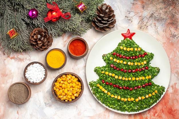 明るい背景に調味料と新年の木の形でトップビューおいしいグリーンサラダ