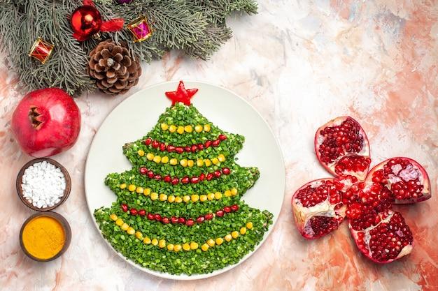 Вид сверху вкусный зеленый салат в форме новогодней елки с приправами на светлом столе праздничная еда здоровье рождественская цветная фотография