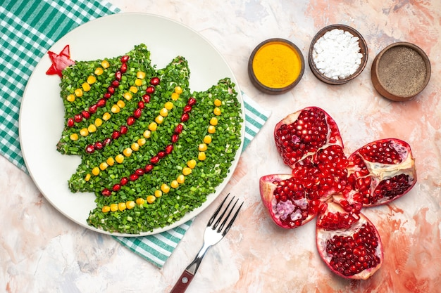 明るい床の色の写真の食事の休日の健康のクリスマスに調味料と新年の木の形の上面図おいしいグリーンサラダ