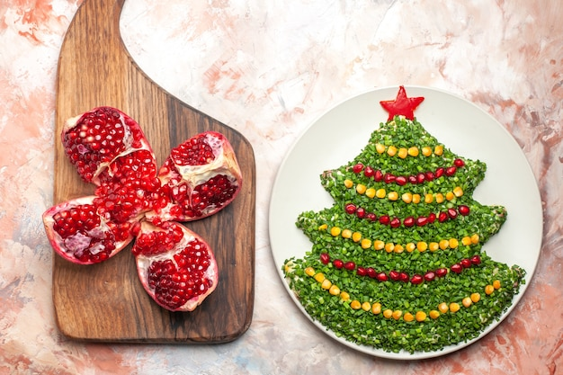 Top view tasty green salad in new year tree shape inside plate on light background