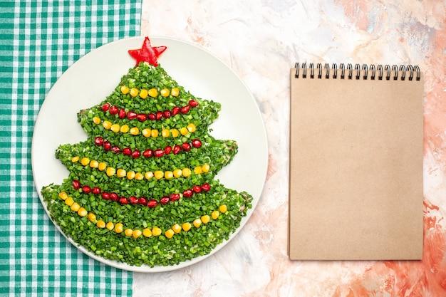 Vista dall'alto gustosa insalata verde a forma di albero di capodanno su sfondo chiaro