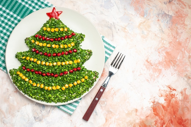 Top view tasty green salad in new year tree shape on light background
