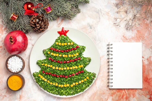 Top view tasty green salad in new year tree shape with seasonings on a light background