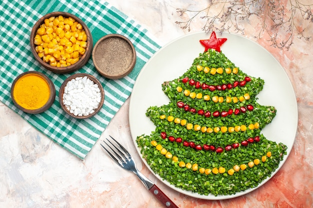 Top view tasty green salad in new year tree shape with seasonings on light background