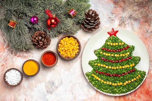 俯视美味的绿色沙拉在新年树形状与调味料光背景