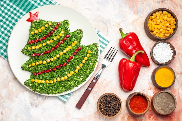 Top view tasty green salad in new year tree shape with seasonings on the light background