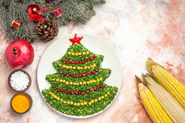Vista dall'alto gustosa insalata verde a forma di albero di capodanno con condimenti su sfondo chiaro