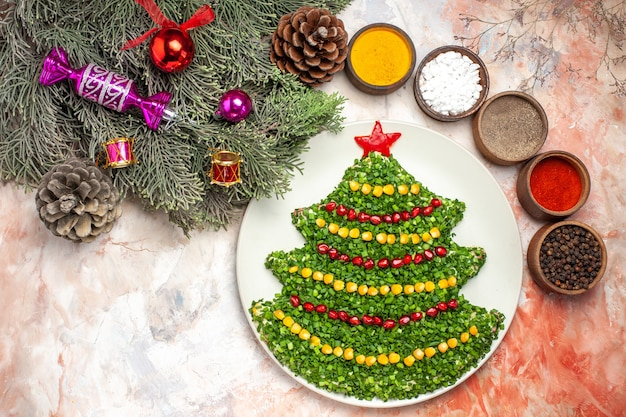 Top view tasty green salad in new year tree shape with seasonings on light desk holiday color photo meal health xmas