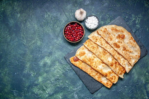 상위 뷰 맛있는 구타브는 어두운 배경 페이스트리에 고기를 넣은 얇은 맛있는 핫케이크 파이 케이크 식사 색상 반죽 오븐을 굽습니다
