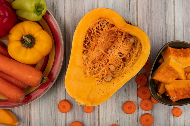 Top view of tasty half pumpkin with colorful bell peppers on a plate with carrots with pumpkin slices on a bowl with chopped carrots isolated on a grey wooden surface