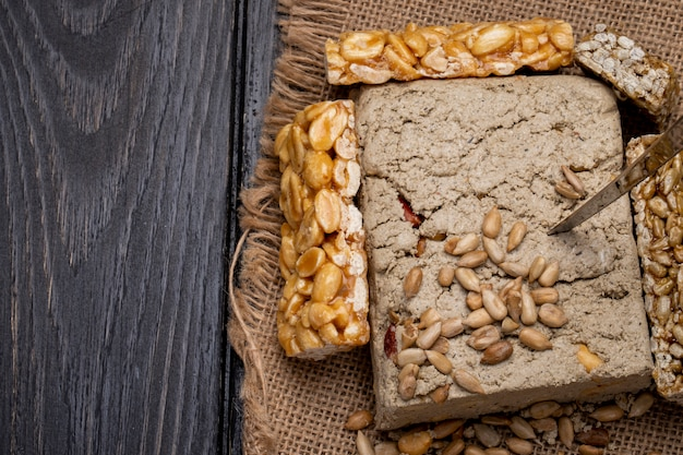 Top view of tasty halva with honey bars with peanuts and sunflower seeds on sackcloth