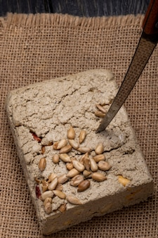 Top view of tasty halva with a knife and sunflower seeds on a sackcloth