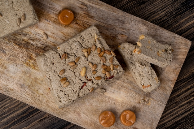 Top view of tasty halva with sunflower seeds on a wooden board