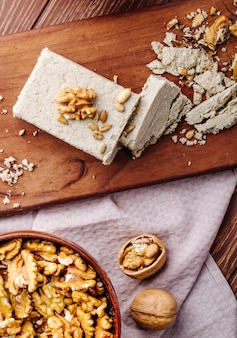 Top view of tasty halva with walnuts on a wooden board
