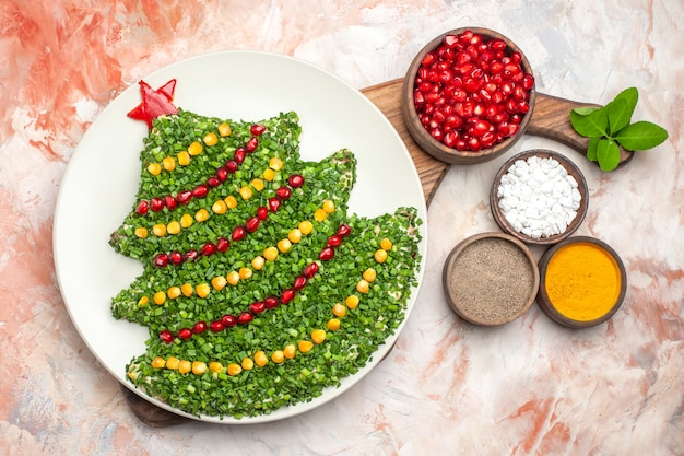 Top view tasty holiday salad in christmas tree shape on light floor