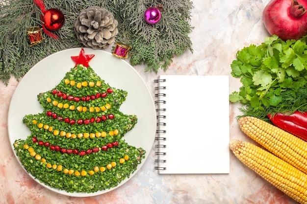 Вид сверху вкусный праздничный салат в форме елки на светлом фоне