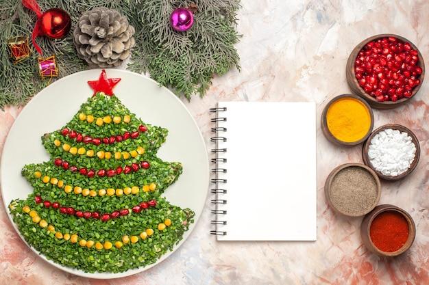 밝은 배경에 조미료와 크리스마스 트리 모양의 상위 뷰 맛있는 휴일 샐러드