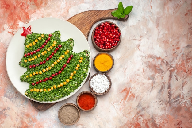 明るい背景に調味料と新年の木の形でトップビューのおいしいホリデーサラダ