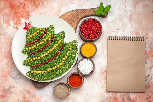 Top view tasty holiday salad in new year tree shape with seasonings on light background