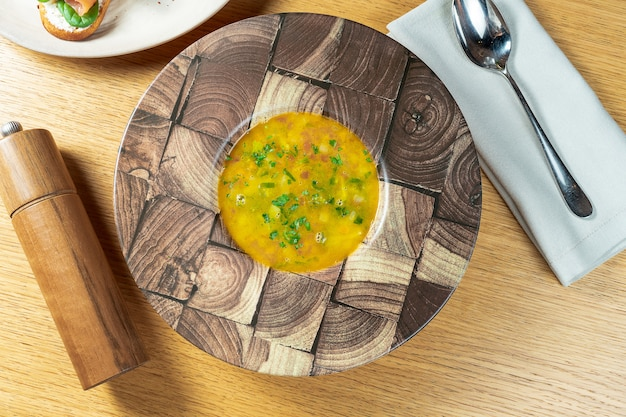 Top view on tasty italian homemade minestrone soup in wooden bowl on wooden background. food photo flat lay.