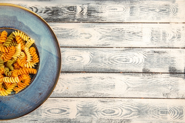 Top view tasty italian pasta unusual cooked spiral pasta on a grey wooden desk