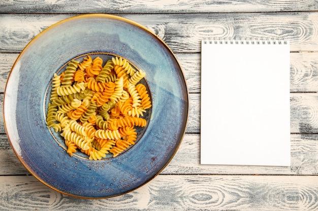 Vista dall'alto gustosa pasta italiana insolita pasta a spirale cotta su grigio