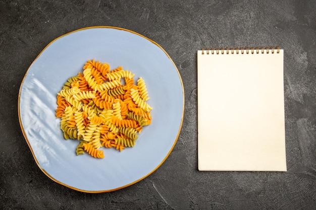 어두운 책상에 상위 뷰 맛있는 이탈리아 파스타 특이한 요리 나선형 파스타