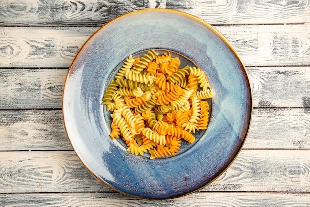 Вид сверху вкусная итальянская паста необычная приготовленная спиральная паста на сером деревянном