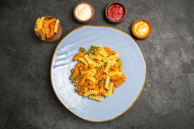 Вид сверху вкусная итальянская паста необычная приготовленная спиральная паста с приправами на сером