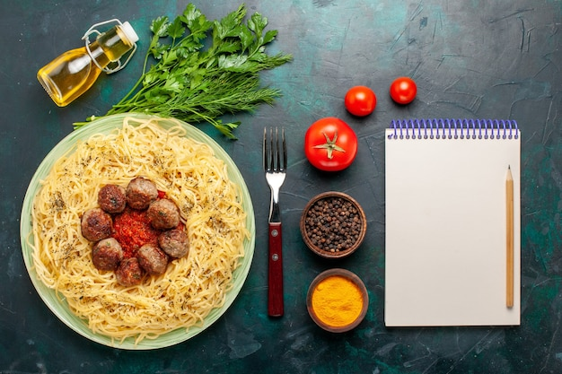 Вид сверху вкусной итальянской пасты с фрикадельками и разными приправами на темно-синем фоне