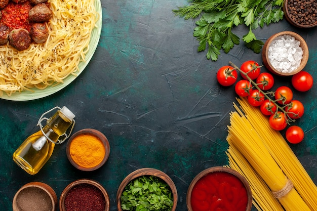 Вид сверху вкусной итальянской пасты с фрикадельками и разными приправами на темно-синем столе