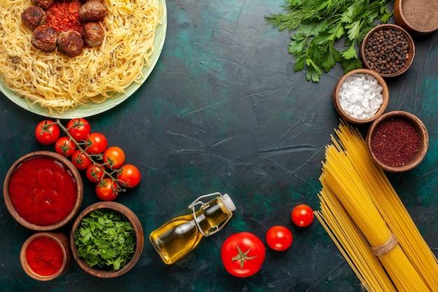 Vista dall'alto gustosa pasta italiana con polpette di carne e diversi condimenti sulla scrivania blu