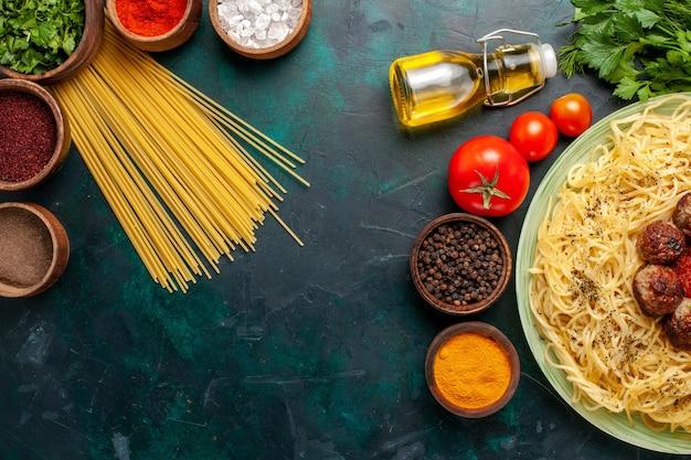 Vista dall'alto gustosa pasta italiana con polpette di carne e condimenti diversi sulla scrivania blu scuro