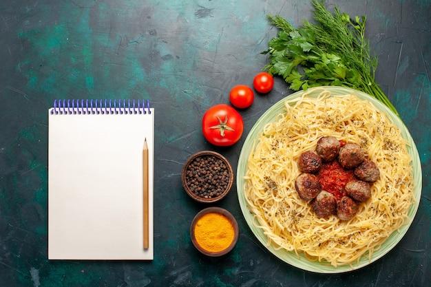 ミートボールのメモ帳と紺色の背景にさまざまな調味料を使ったトップビューのおいしいイタリアンパスタ
