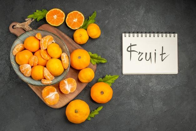 Top view tasty juicy tangerines inside plate on dark background