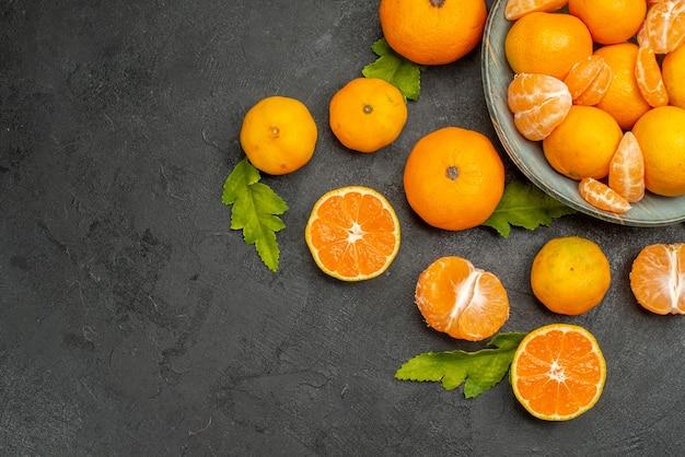 Вид сверху вкусные сочные мандарины внутри тарелки на темном фоне