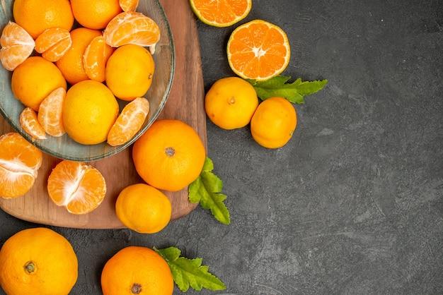 Вид сверху вкусные сочные мандарины внутри тарелки на сером фоне